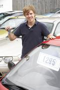 Young man collecting new car - stock photo