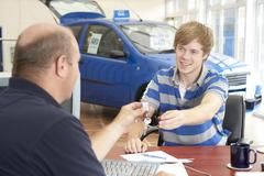 Young man filling in paperwork in car showroom Stock Photos