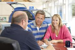Couple filling in paperwork in car showroom Stock Photos