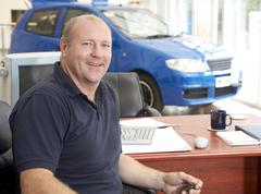 Car salesman sitting in showroom smiling Stock Photos