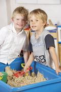 Two Young Boys Playing Together in Sandpit - stock photo