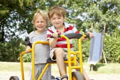 Two Young Boys Playing on Bike Stock Photos
