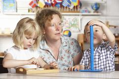 Adult Helping Two Young Children at Montessori/Pre-School Stock Photos