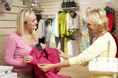 Sales assistant with customer in clothing store Stock Photos