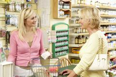 Female sales assistant in health food store Stock Photos
