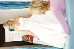 Bride trying on wedding dress with sales assistant Stock Photos