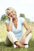 Portrait of mature woman sitting in countryside Stock Photos
