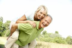 Mature couple having fun in countryside Stock Photos