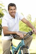 Young man riding bike in countryside Stock Photos