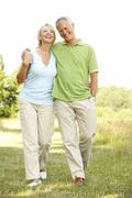 Mature couple walking in countryside - stock photo