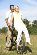 Young couple riding bike in countryside - stock photo