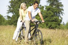 Couple riding tandem in countryside - stock photo