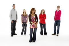 full length studio portrait of five teenage friends - stock photo