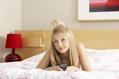 teenage girl in bedroom with mobile phone - stock photo