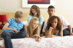 group of five teenage friends looking bored in bedroom - stock photo