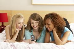 Group of three teenage girls using mobile phone in bedroom Stock Photos
