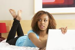 guilty teenage girl using laptop in bedroom - stock photo