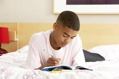 Teenage boy writing in diary in bedroom Stock Photos