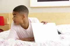 guilty teenage boy using laptop in bedroom - stock photo