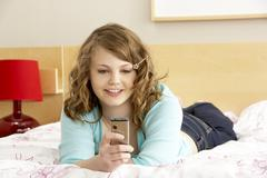Teenage girl in bedroom with mobile phone Stock Photos
