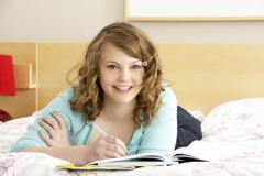 Teenage girl writing in diary in bedroom Stock Photos