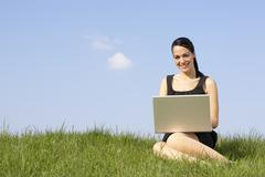 woman using laptop outdoors in summer countryside - stock photo