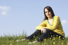 teenage girl sitting in summer meadow - stock photo