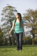 Teenage girl walking through summer meadow Stock Photos
