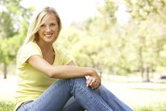 portrait of young woman sitting in park - stock photo
