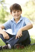 Stock Photo of portrait of young boy sitting in park