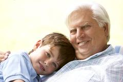Grandfather hugging grandson in park Stock Photos