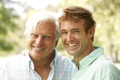 portrait of senior man with adult son - stock photo