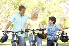 Parents and son on cycle ride in park Stock Photos