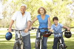 grandparents and grandson on cycle ride in park - stock photo