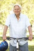senior man on cycle ride in park - stock photo