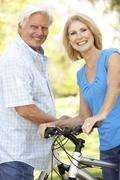 senior couple on cycle ride in park - stock photo