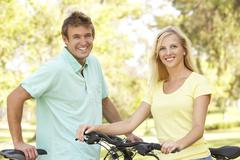 young couple on cycle ride in park - stock photo