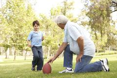 grandfather and grandson playing american football together - stock photo