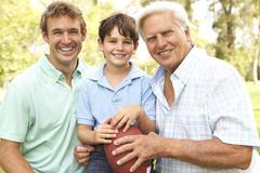 Grandfather with father and son playing american football together Stock Photos