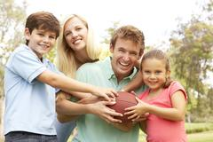 Family playing american football together in park Stock Photos