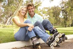 Couple putting on in line skates in park Stock Photos