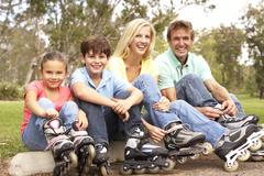 family putting on in line skates in park - stock photo
