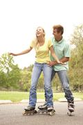 Couple wearing in line skates in park Stock Photos