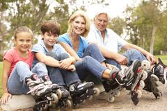 Grandparents and grandchildren putting on in line skates in park Stock Photos