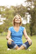 senior woman relaxing in park - stock photo