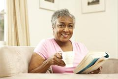 Stock Photo of senior woman reading book with drink at home