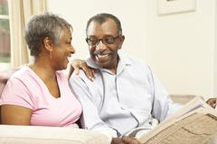 senior couple reading newspaper at home - stock photo