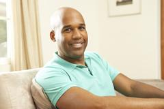 man relaxing on sofa at home - stock photo