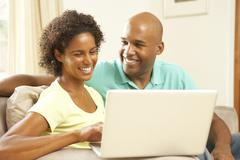 couple using laptop at home - stock photo
