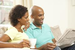 couple relaxing at home with newspaper - stock photo